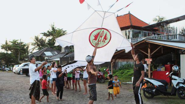 PHOTO: Girls and boys from the project's pilot village, Pererenan, help fly a giant kite carrying the Bye Bye Plastic Bags logo, to increase awareness, Bali, Indonesia. (Paola Gianturco )