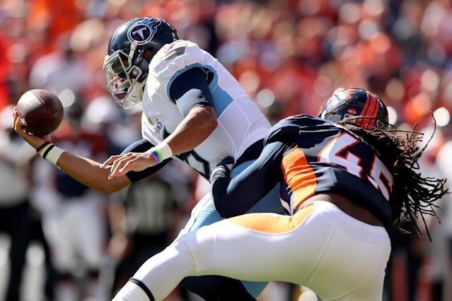 Quarterback Marcus Mariota of the Tennessee Titans is sacked by Alexander Johnson of the Denver Broncos. (Getty Images)