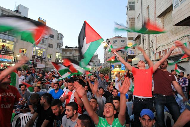 Palestinians celebrate in the West Bank city of Ramallah on May 30, 2014, after Palestine qualified for their maiden Asian Cup appearance with a 1-0 win over injury-hit Philippines in the final of the AFC Challenge Cup in Maldives (AFP Photo/Abbas Momani)