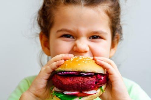 """<span class=""""caption"""">There's more behind that vegan burger than it seems.</span> <span class=""""attribution""""><a class=""""link rapid-noclick-resp"""" href=""""https://www.shutterstock.com/image-photo/happy-hungry-child-girl-eating-healthy-585528380?src=a78c5a5f-ea93-43b0-9eb7-51cf480c13e2-1-41"""" rel=""""nofollow noopener"""" target=""""_blank"""" data-ylk=""""slk:Nina Firsova/Shutterstock.com"""">Nina Firsova/Shutterstock.com</a></span>"""
