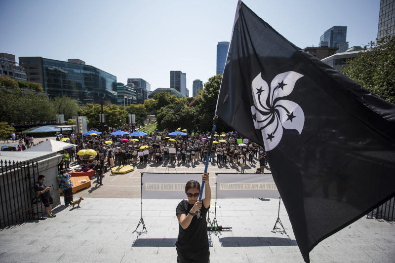 """FILE - In this Aug. 3, 2019, file photo, a woman holds a """"Black Bauhinia"""" flag, a symbol of the Hong Kong rebellion, during a rally in support of Hong Kong anti-extradition bill protesters, in Vancouver, British Columbia. Governments around the world are taking a cautious approach to responding to the protests roiling Hong Kong. With the notable exception of Taiwan, cautious comments from a handful of governments fall short of support for the demonstrators. They are so mild that even the word """"protest"""" itself was left out of the joint EU-Canada statement that was the most recent to infuriate the Chinese government. Most are unwilling to risk that fury at all, showing China's deep influence around the world.(Darryl Dyck/The Canadian Press via AP)"""