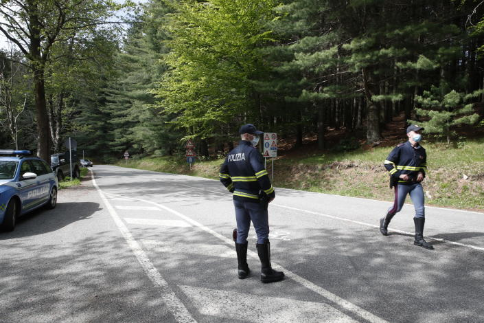 Police officers patrol the road leading to the Stresa-Mottarone cable line for rescue operations to take place after a cable car of the line collapsed, near Stresa, Italy, Sunday, May 23, 2021. A cable car taking visitors to a mountaintop view of some of northern Italy's most picturesque lakes plummeted to the ground Sunday and then tumbled down the slope, killing at least 13 people and sending two children to the hospital, authorities said. (AP Photo/Antonio Calanni)