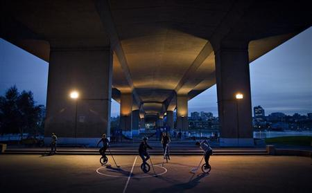 Group of young men play hockey on unicycles in Vancouver, British Columbia