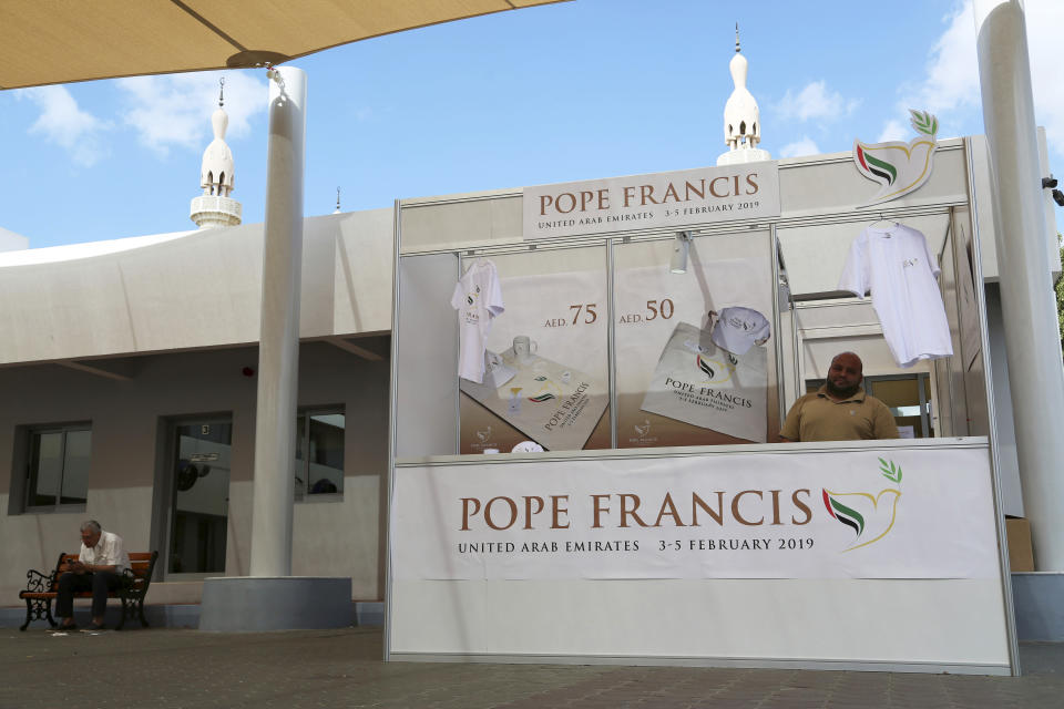 In this Sunday, Jan. 20, 2019 photo, a man sells memorabilia for Pope Francis' upcoming trip to the United Arab Emirates at St. Mary's Catholic Church in Dubai, United Arab Emirates. The minarets of a mosque can be seen behind his stand. The Catholic Church's parishioners in the UAE come from around the world and will offer an international welcome to Pope Francis on his visit Feb. 3 through Feb. 5. It is the first papal visit in history to the Arabian Peninsula, the birthplace of Islam. (AP Photo/Jon Gambrell)