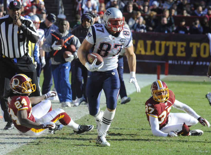New England Patriots tight end Rob Gronkowski (87) runs past Washington Redskins strong safety DeJon Gomes (24) and Washington Redskins free safety Reed Doughty (37) during the first half of an NFL football game on Sunday, Dec. 11, 2011, in Landover, Md.  (AP Photo/Rich Lipski)