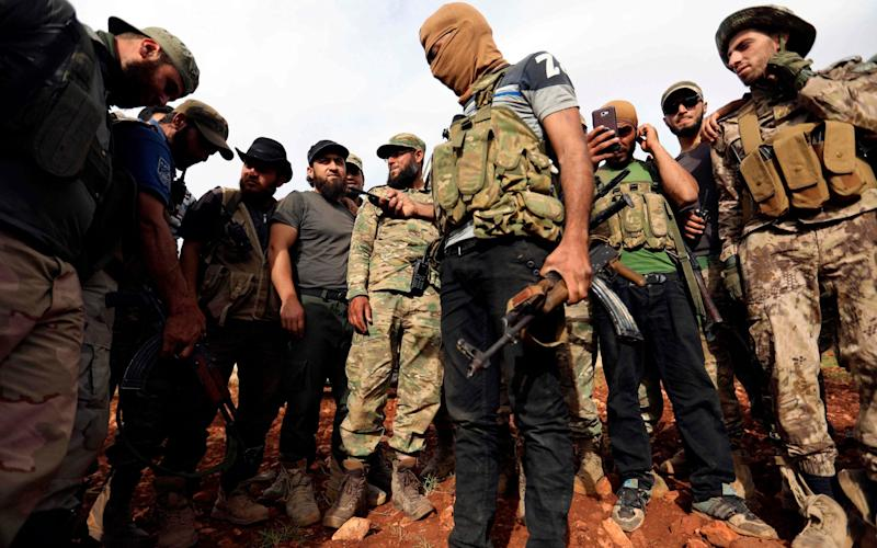Syrian rebels gather in a field in the northern countryside of Hama province during clashes with regime forces - AFP
