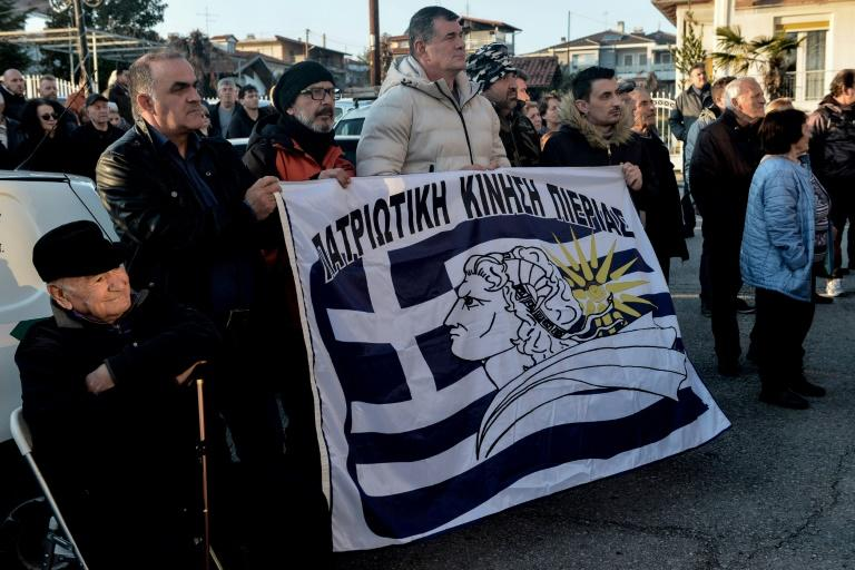"""Inhabitants hold a banner reading """"Patriotic Movement of Pieria"""" as they gather outside the town hall during a protest against the creation of a migrants' hosting centre, in Makrigialos, a beachfront tourist village, some 460km north of Athens"""