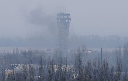 Smoke rises near the traffic control tower of the Sergey Prokofiev International Airport damaged by shelling during fighting between pro-Russian separatists and Ukrainian government forces, in Donetsk