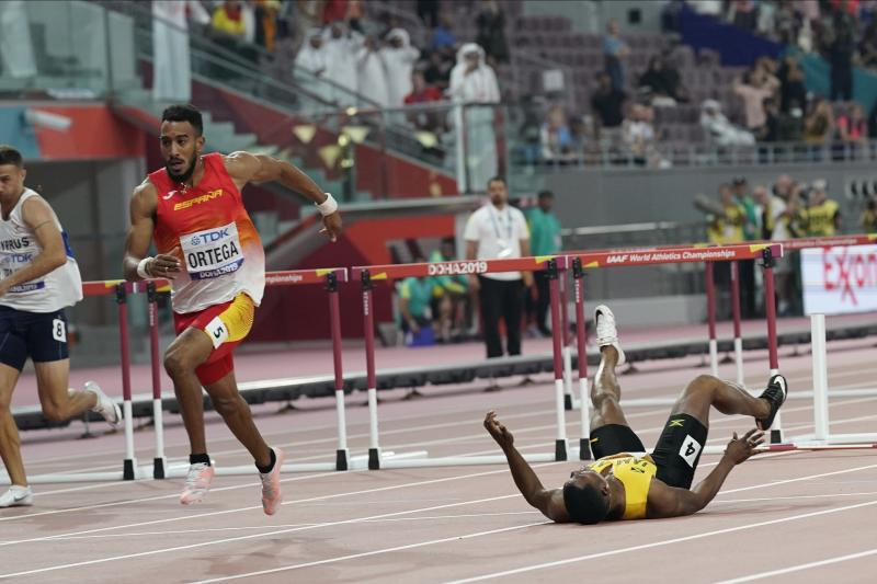 Omar Mcleod, of Jamaica, right, falls as Orlando Ortega, of Spain, finishes the the men's 110 meter hurdles final during the World Athletics Championships in Doha, Qatar, Wednesday, Oct. 2, 2019. (AP Photo/David J. Phillip)