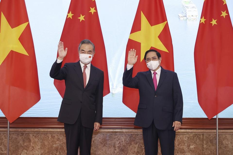 Vietnamese Prime Minister Pham Minh Chinh and Chinese Foreign Minister Wang Yi wave as they stand for photos in Hanoi, Vietnam on Saturday, Sep.11, 2021. China has pledged to donate 3 million doses of its vaccine to Vietnam as Foreign Minsiter Wang Yi closed his visit to Hanoi. (Duong Van Giang/VNA via AP)