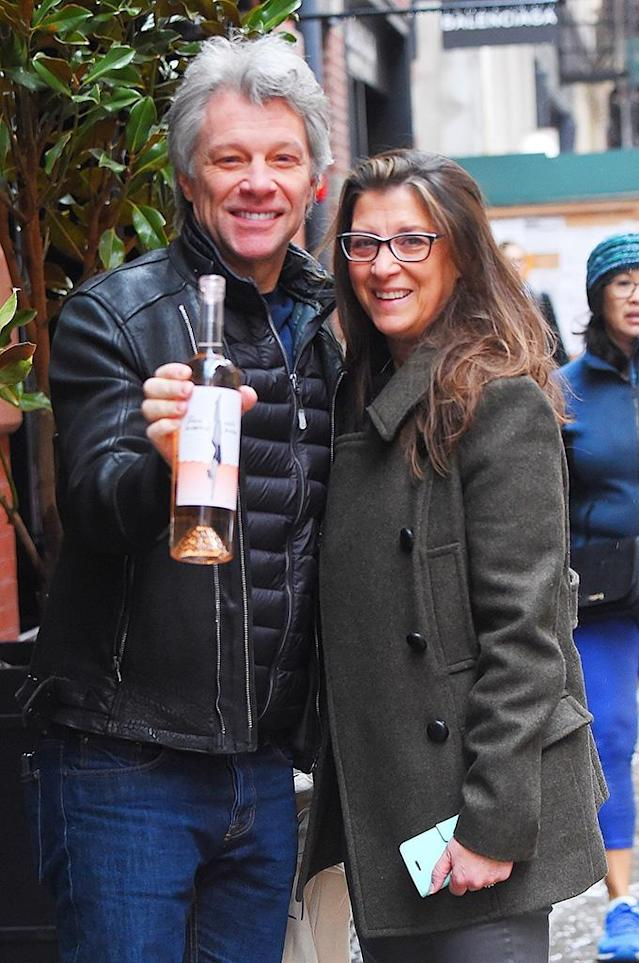 <p>The New Jersey rocker showed off his brand-new, not yet launched, rosé wine, €œHampton Waters, while out with his wife, Dorothea Hurley, in New York City on Monday. (Photo: Backgrid) </p>