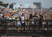 A group of people on a bridge with Large Crowds gathering behind them at Southend beach as temperatures soar to as high as 34 degrees across the UK.