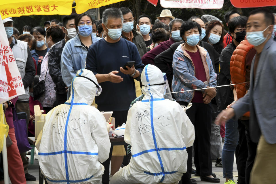 In this photo released by Xinhua News Agency, residents wearing face masks to help curb the spread of the coronavirus line up for the COVID-19 test near the residential area in Qingdao in east China's Shandong province on Tuesday, Oct. 13, 2020. China says it has carried out more than 4.2 million tests in the northern port city of Qingdao, with no new cases of coronavirus found among the almost 2 million sets of results received. (Li Ziheng/Xinhua via AP)