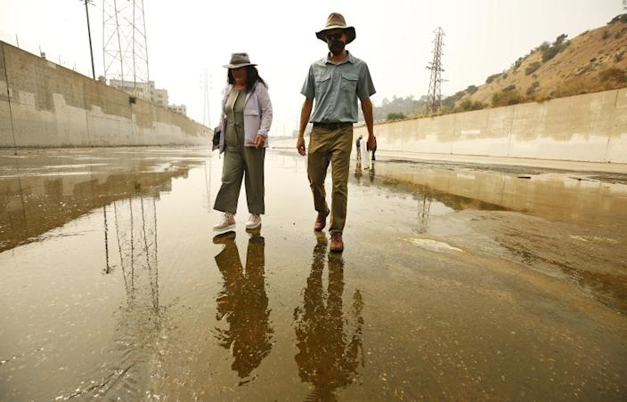 LOS ANGELES, CA - SEPTEMBER 15: Wendy Katagi, left, Senior Manager, Watershed and Ecosystem Restoration Services at Stillwater Sciences and Isaac Brown, D.Env. Senior Scientist at Stillwater Sciences meet with a group of biologists, engineers and LA City Hall officials as they do field work in the Los Angeles River channel with proposals for putting deeper, colder flows, riffles and pools back into a 4.8-mile stretch of the river downtown in an effort to bring endangered steelhead trout back to the L.A. River. The Los Angeles River Fish Passage and Habitat Structures Design Plan will create a migratory passageway for federally endangered steelhead cruising upstream to ancestral spawning grounds in the river's soft-bottom sections north of downtown. Los Angeles River on Tuesday, Sept. 15, 2020 in Los Angeles, CA. (Al Seib / Los Angeles Times