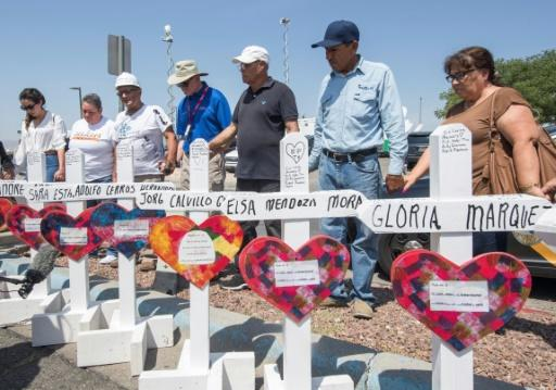 People pray beside crosses with the names of victims of a shooting in El Paso, Texas that left 22 people dead