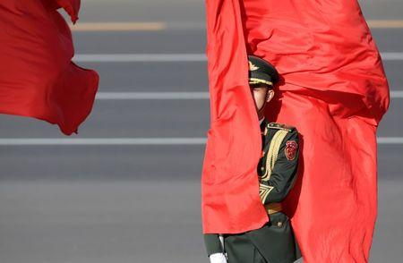 A soldier from honour guards holds a red flag during a welcoming ceremony in Beijing