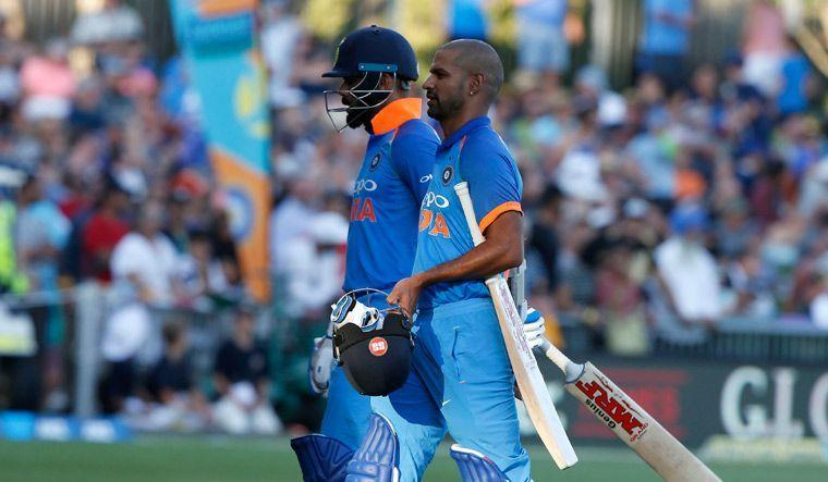 Kohli and Dhawan walking off the field as play was stopped due to excessive sunlight