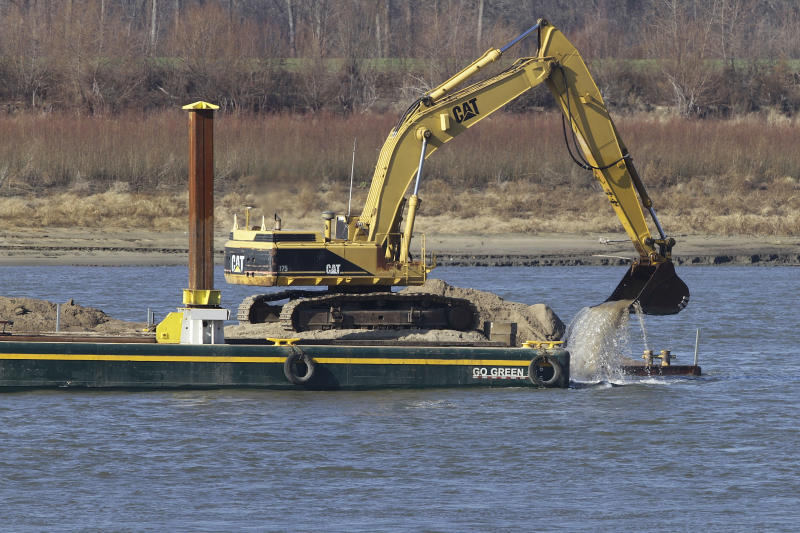 Barges with excavating machinery remove rocks on the Mississippi River Tuesday, Dec. 18, 2012, in Thebes Ill. The Army Corps of Engineers is delaying the use of explosives to blast away treacherous rock pinnacles on the Mississippi River because crews are having so much success removing the rocks with excavating machinery. (AP Photo/Seth Perlman)