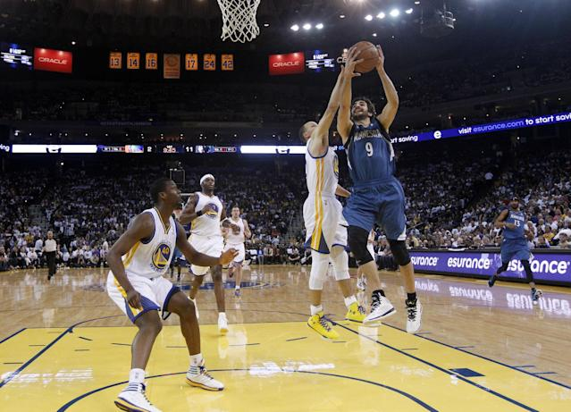 Minnesota Timberwolves' Ricky Rubio (9) drives to the basket a Golden State Warriors' Stephen Curry, center, defends during the first half of an NBA basketball game on Monday, April 14, 2014, in Oakland, Calif. (AP Photo/Marcio Jose Sanchez)