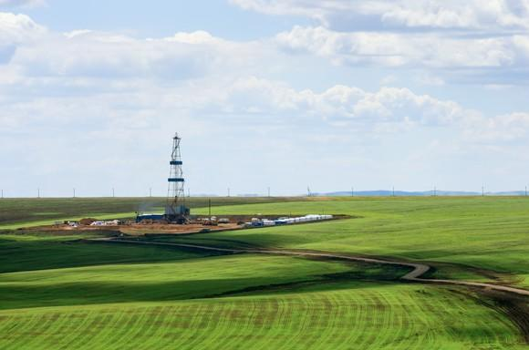 A drilling rig in the middle of a green field.