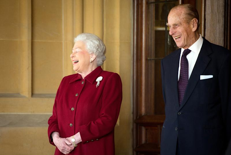 Britain's Queen Elizabeth and Prince Philip laugh after bidding farewell to the President of Ireland Michael D. Higgins and his wife Sabina at Windsor Castle in Windsor, southern England April 11, 2014. The Irish President and his wife Sabina left Windsor at the end of a four day State Visit to Britain, during which they stayed at Windsor Castle as guests of Queen Elizabeth. REUTERS/Leon Neal/Pool (BRITAIN - Tags: ENTERTAINMENT SOCIETY ROYALS)