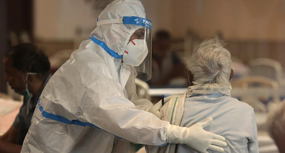Medical worker in PPE with patient.