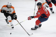Washington Capitals right wing Anthony Mantha (39) and Philadelphia Flyers center Claude Giroux (28) vie for the puck during the first period of an NHL hockey game Tuesday, April 13, 2021, in Washington. The Capitals won 6-1. (AP Photo/Nick Wass)