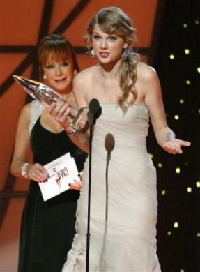 Taylor Swift accepts the award for Entertainer of the Year from presenter Reba McEntire (L) at the 45th Country Music Association Awards in Nashville, Tennessee, November 9, 2011.