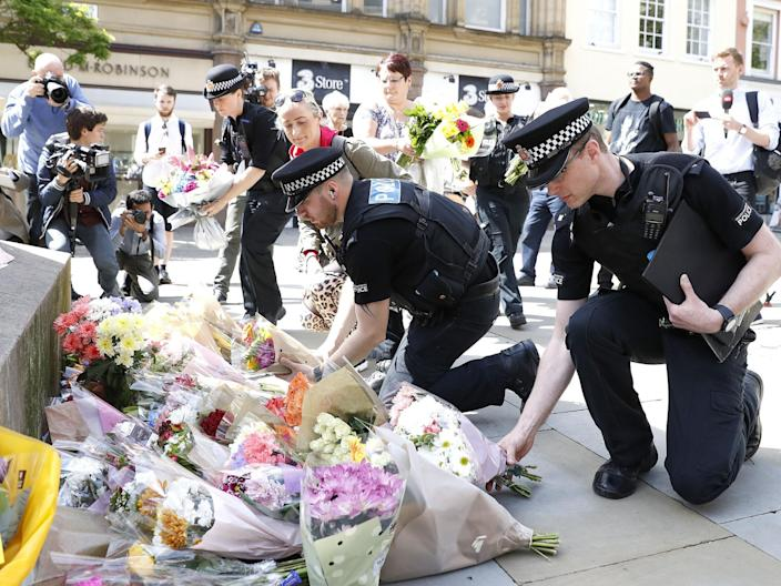 Police officers laying flowers in St Ann's Square, Manchester, the day after a suicide bomber killed 22 people, including children, as an explosion tore through fans leaving a pop concert in Manchester (PA)