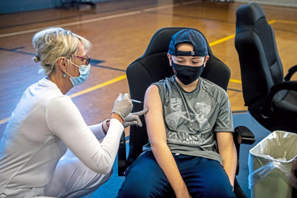 Linda Zeigler, of nurse with St. Clair Health, administers the Pfizer COVID-19 vaccine to Jameson Cooley, 12, of Shadyside in Pittsburgh, Pa., at a clinic organized by St. Clair Health and the Carnegie Boys and Girls Club to vaccinate youth ages 12 and older, Saturday, May 15, 2021, in Carnegie, Pa. (Alexandra Wimley/Pittsburgh Post-Gazette via AP)
