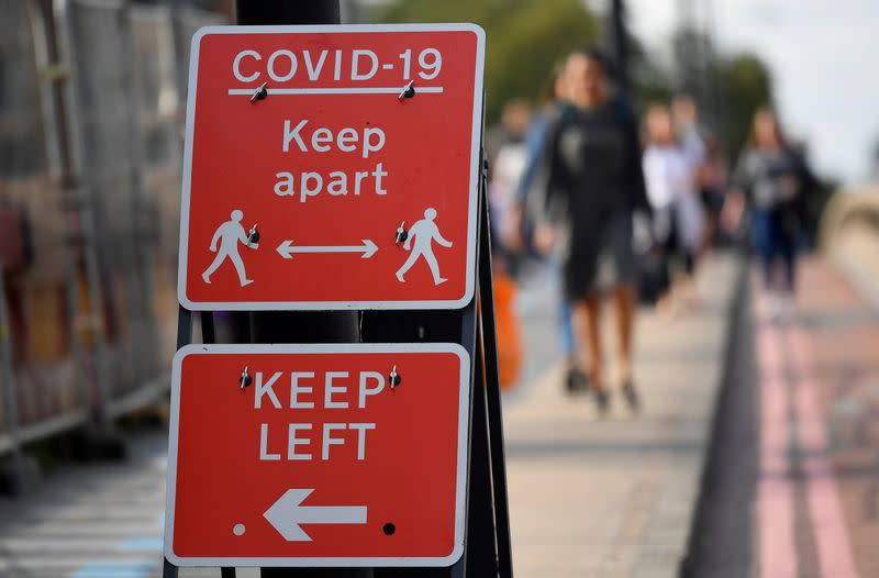 "FILE PHOTO: Pedestrians walk near public health signs, whilst the reproduction ""R"" number of COVID-19 infections in the United Kingdom has risen and may be above 1, London, Britain"