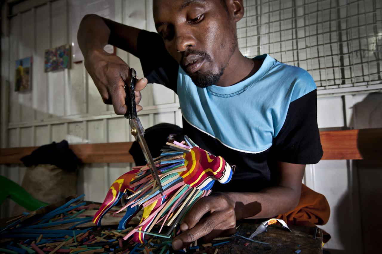 In this photo taken Monday, April 29, 2013, carver Daniel Lekalau, 26, uses scissors to trim the mane of a toy lion he is making from pieces of discarded flip-flops, at the Ocean Sole flip-flop recycling company in Nairobi, Kenya. The company is cleaning the East African country's beaches of used, washed-up flip-flops and the dirty pieces of rubber that were once cruising the Indian Ocean's currents are now being turned into colorful handmade giraffes, elephants and other toy animals. (AP Photo/Ben Curtis)