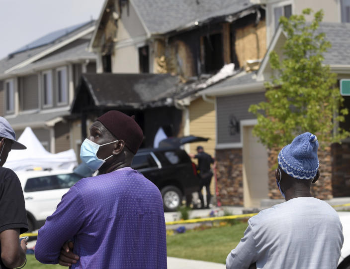 Amadou Deh stands in front of the remnants of a house fire that killed five people in suburban Denver on Wednesday, Aug. 5, 2020. Three people escaped the fire by jumping from the home's second floor. Investigators believe the victims were a toddler, an older child and three adults. Authorities suspect was intentionally set. (AP Photo/Thomas Peipert)