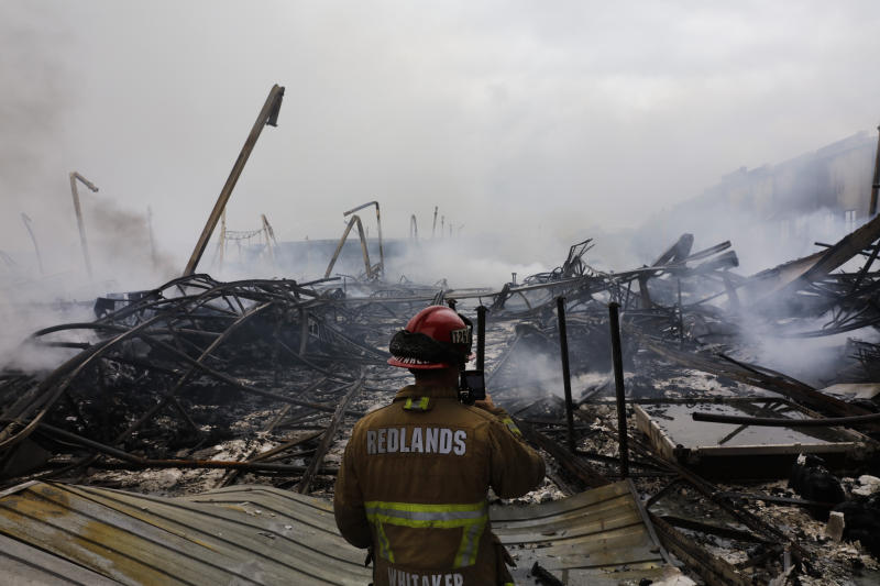 Redlands Fire Capt. Dustin Whitaker surveys damages at a warehouse destroyed in a fire Friday, June 5, 2020, in Redlands, Calif. The fire destroyed the Southern California distribution facility that was used to ship items to Amazon customers but authorities said employees got out and there were no reports of injuries. (AP Photo/Jae C. Hong)