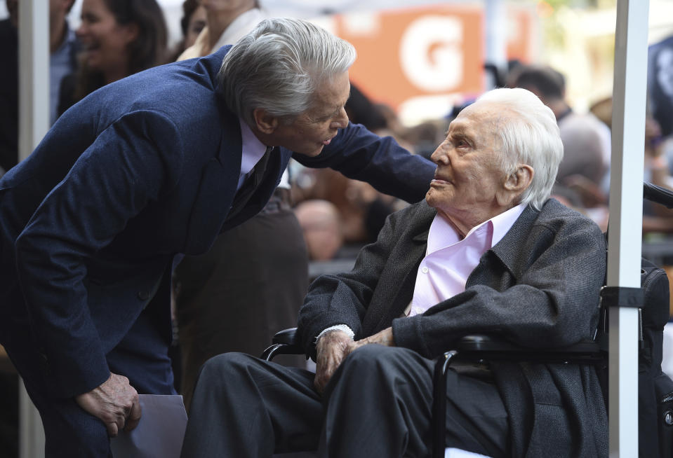 Michael Douglas, left, speaks with his father Kirk Douglas before a Hollywood Walk of Fame star ceremony (Photo by Chris Pizzello/Invision/AP)