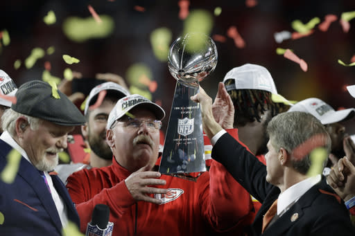 FILE - In this Feb. 2, 2020, file photo, Kansas City Chiefs chairman Clark Hunt, right, hands the trophy to head coach Andy Reid after the chiefs defeated the San Francisco 49ers in the NFL Super Bowl 54 football game in Miami Gardens, Fla. It's hard enough when things are normal only seven franchises have won back-to-back championships. But it's even more difficult when the offseason has been thrown into turmoil because of the coronavirus pandemic, affecting everything from free agency to the NFL draft to team workouts that should have begun this month, but will not. (AP Photo/Chris O'Meara, File)