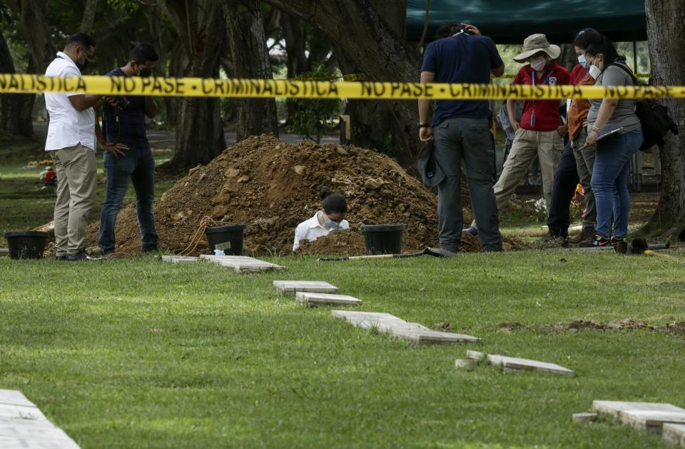 Forensic workers exhume what are believed to be the remains of Lt. Braulio Bethancourt, a victim of the 1989 U.S. invasion, at the Jardin de Paz cemetery in Panama City, Thursday, April 15, 2021. The prosecutor's office has begun an exhumation of human remains at the Panamanian cemetery in a renewed attempt to confirm the identities of the victims of the U.S. invasion. (AP Photo/Arnulfo Franco)