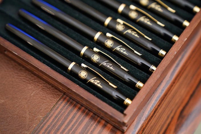 FILE - In this Jan. 21, 2021, file photo pens featuring President Joe Biden's signature and presidential seal, are displayed in the State Dinning Room of the White House in Washington. (AP Photo/Alex Brandon, File)