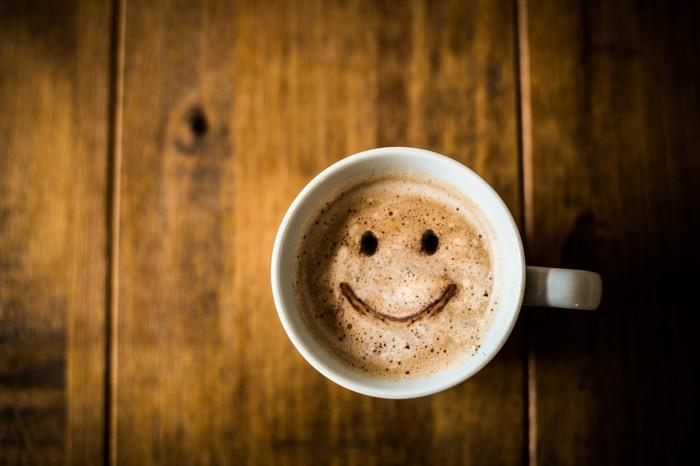 A smiley face made out of coffee and milk inside a coffee mug