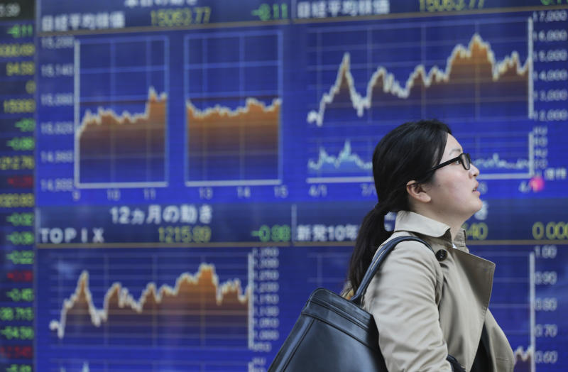 A woman walks by an electronic stock board of a securities firm in Tokyo, Friday, April 4, 2014. Asian stock markets were little changed Friday after the European Central Bank refrained from further easing of monetary policy and investors looked to the upcoming U.S. jobs report for a new trading cue. Tokyo's Nikkei 225 edged up 0.1 percent to 15,091.33. (AP Photo/Eugene Hoshiko)