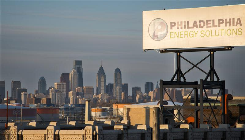 The Philadelphia Energy Solutions oil refinery owned by The Carlyle Group is seen at sunset in front of the Philadelphia skyline