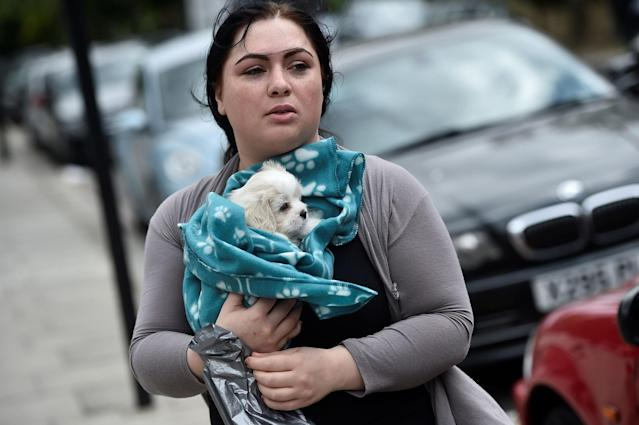 <p>A woman carries a dog from the Dorney Tower residential block, as residents were evacuated as a precautionary measure following concerns over the type of cladding used on the outside of the buildings on the Chalcots Estate in north London, Britain, June 25, 2017. (Photo: Hannah McKay/Reuters) </p>