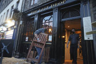 A man stacks away chairs outside The Last Drop pub, as temporary restrictions announced by First Minister Nicola Sturgeon to help curb the spread of coronavirus have come into effect from 6pm, in Edinburgh, Friday, Oct. 9, 2020. (Andrew Milligan/PA via AP)