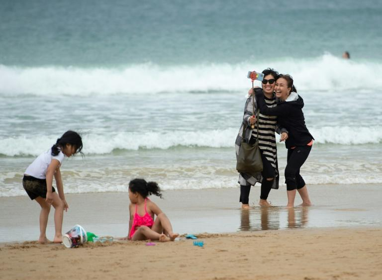 Two women smile as they take a selfie photo on La Concha beach in the Basque resort of San Sebastian after the state of emergency was lifted