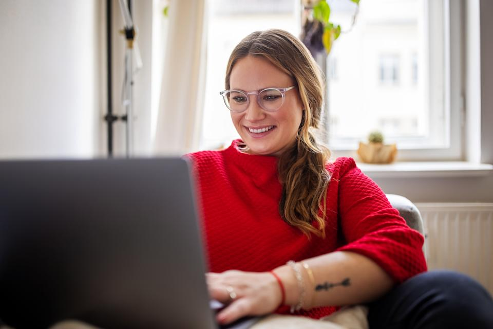 Happy woman sitting on sofa and working on laptop computer. Smiling female working at home.