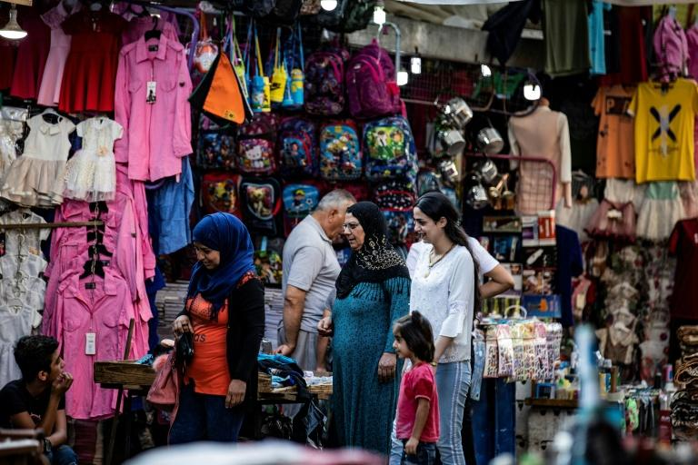 People stroll through a market in the Kurdish-majority city of Qamishli in northeast Syria (AFP Photo/Delil SOULEIMAN)