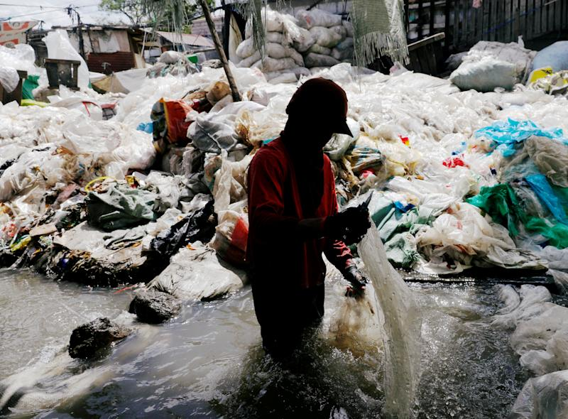 File Photo: A man washes plastic for recycling in a murky pond at Payatas district, Quezon City, Metro Manila, Philippines January 21, 2018. REUTERS/Dondi Tawatao TPX IMAGES OF THE DAY