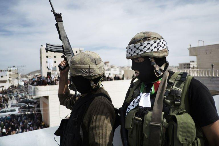 "Palestinian militants of the Al-Aqsa Martyrs Brigades stand guard on the roof of a building in the West Bank village of Saair on February 25, 2013. Gaza militants from Fatah's Al-Aqsa Martyrs Brigades have fired a rocket at Israel in a ""preliminary"" step after one of its men died following an Israeli interrogation"