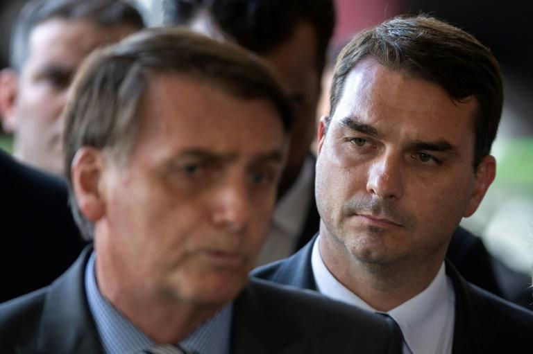 President Jair Bolsonaro's son Flavio (R, with his father, L) has been charged with corruption
