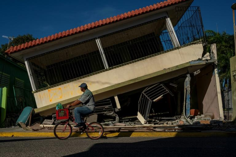 A man rides his bicycle past a collapsed house in Guanica, Puerto Rico on January 15, 2020, after a powerful earthquake hit the island (AFP Photo/Ricardo ARDUENGO)